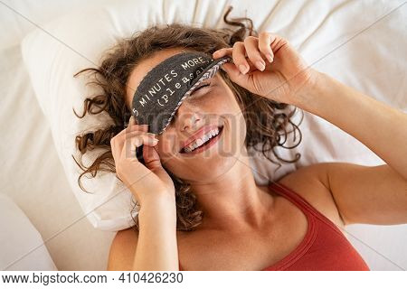 Top view of tired young woman sleeping on bed. Close up face of beautiful sleepy girl wearing funny eye mask while peeping with one eye. High angle view of woman covering her eyes with sleeping mask.