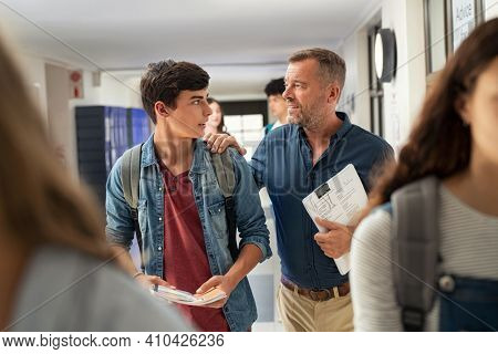 Mature man talking to high school student in hallway at the end of the lesson. Senior professor in conversation with guy student in campus. Teacher talking to encourage young man after exam.