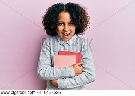 Young little girl with afro hair holding books smiling and laughing hard out loud because funny crazy joke.