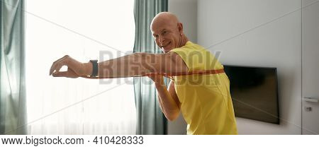 Athletic Man Practicing Punching With A Elastic Band. Self-isolation Trainer Training With Elastic B