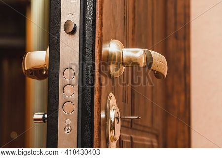 Close-up Of The Golden Handle, The Lock With The Key Of The Beautiful Brown Front Door