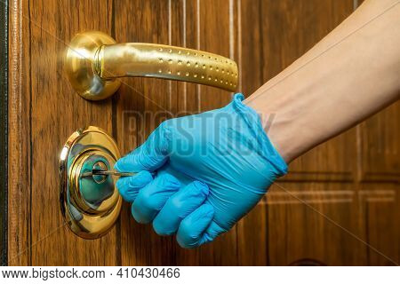 Men's Hands In Blue Gloves Open The Brown Front Door With A Key Close-up
