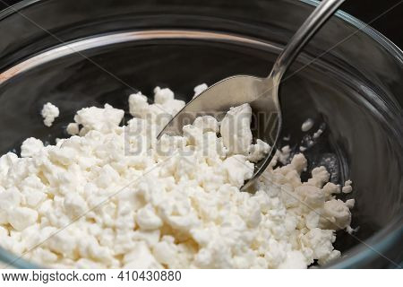 Granulated Cottage Cheese In A Glass Bowl With A Spoon Close-up