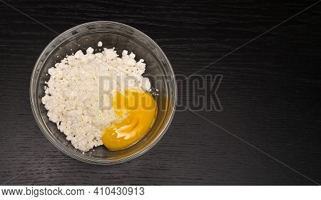 Grainy Cottage Cheese, Egg In A Glass Bowl On A Black Table Close-up With Copy Space, Top View