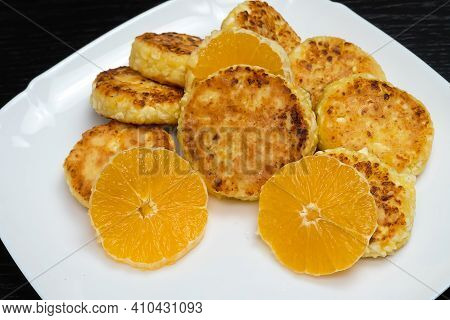 Cottage Cheese Pancake With Orange Slices On A White Plate. Concept Of Delicious Breakfast
