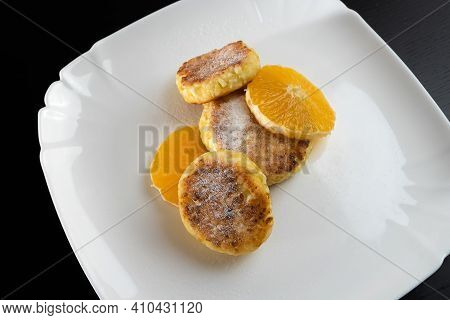 Sweet Cottage Cheese Pancake Sprinkled With Powdered Sugar With Orange Close-up On A White Plate. Co
