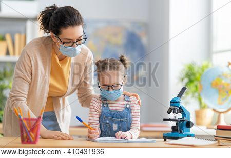 Back to school. Happy child is wearing facemask sitting at desk. Girl with teacher in classroom.