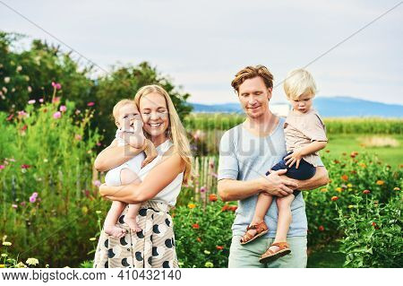 Happy Young Lovely Family With Small Kids Enjoing Nice Day In Summer Park Or Garden With Blooming Fl