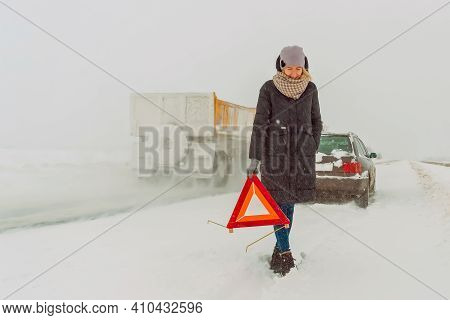 Young Girl In A Jacket, Hat, Scarf, Shoes Puts A Warning Road Sign In A Triangle On A Snow-covered R