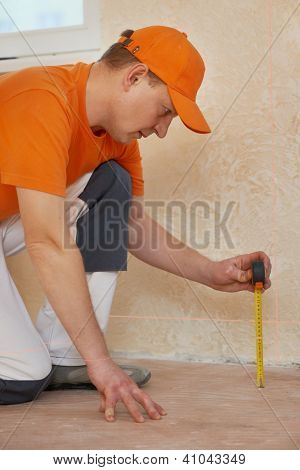 parquet carpenter worker use laser beam level to determine floor problem before installing wood board during flooring work
