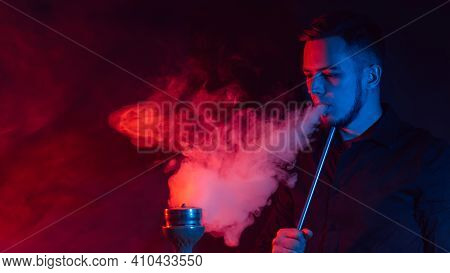 Male Smoker Smokes A Hookah And Lets Out A Cloud Of Smoke