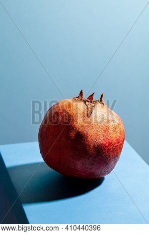 Modern Still Life With Red Pomegranate On Blue Background. Minimal Fruit Composition