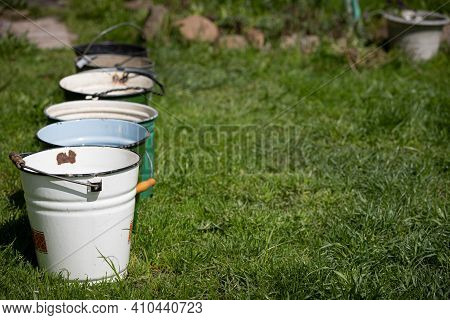 Many Different Buckets Stand In A Row To Collect Rainwater. Buckets Of Water Stand On The Grass In T