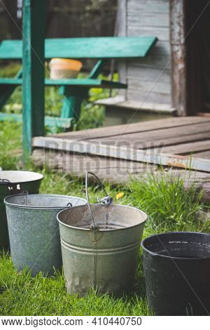 Several Old Buckets Are Standing On The Grass In Sunny Weather. Collecting Rainwater In Buckets In T