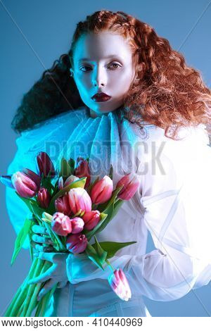 Portrait of a refined fashion model girl with long red curly hair posing in a white haute couture dress with late renaissance ruffled collar and tulips. Art fashion history.