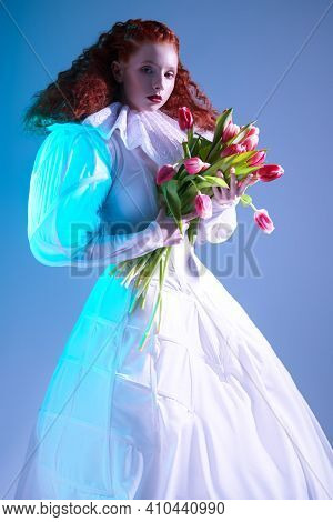 Art fashion history. Portrait of a refined fashion model girl with long red curly hair posing in a white haute couture dress with late renaissance ruffled collar and tulips.