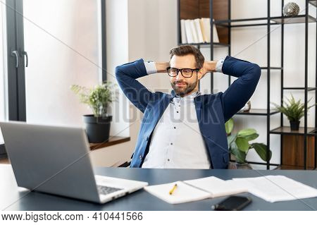 Successful Bearded Young Businessman In Business Wear, Glasses Sitting At The Desk At Home Office, F
