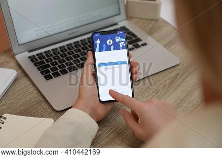 Mykolaiv, Ukraine - August 28, 2020: Woman Holding Iphone 11 With Facebook App On Screen At Table, C