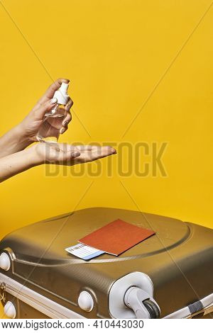 A Person Disinfecting Hands With Antiseptic Gel. Traveling With Suitcase