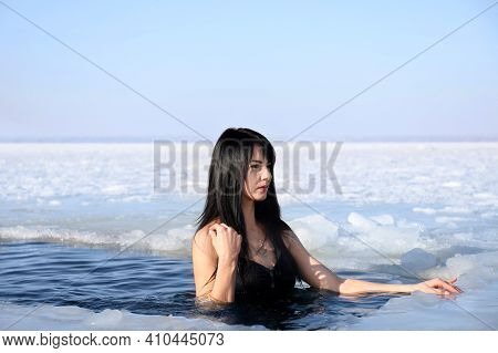 Woman Immersing In Icy Water On Winter Day. Baptism Ritual
