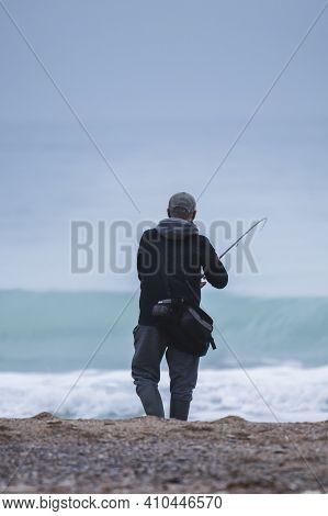 Angler Enjoying His Hobby At The Beach