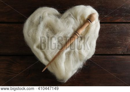Heart Shaped Pile Of White Wool And Spindle On Wooden Table, Top View