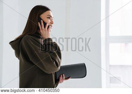 Athletic pleased sportswoman talking on mobile phone before practice indoors