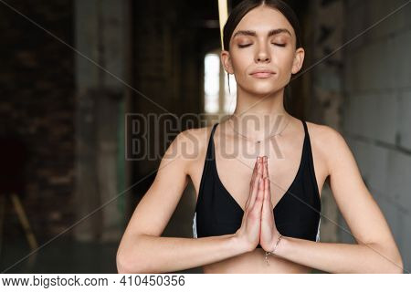 Athletic young sportswoman doing breathing exercise during yoga practice indoors