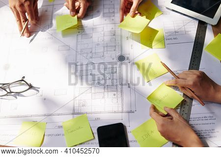 Team Of Architects And Managers Sticking Notes On Building Blueprint When Planning Work
