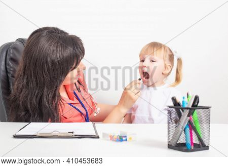 Woman Doctor Pediatrician Examines The Red Throat Of A Little Girl. Sore Throat In Children, Concept