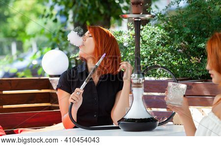 Young Women Smoke A Hookah In A Cafe On The Street