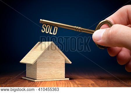 Sold Real Estate Concept With Key. Wooden Model Of House And Key With Text Sold In Hand. Key To Succ