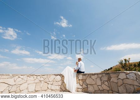 The Bride And Groom Are Sitting On A Stone Fence, The Bride Is Leaning On The Groom, The Groom Gentl
