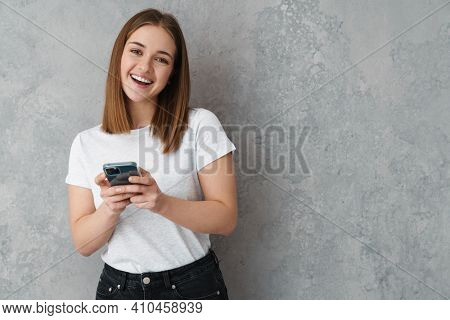 Happy nice charming girl smiling and using cellphone isolated over grey wall