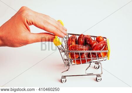 Female Hand Holds Supermarket Trolley With Heap Of Dried Dates. Raw Organic Tasty Dates In Shopping