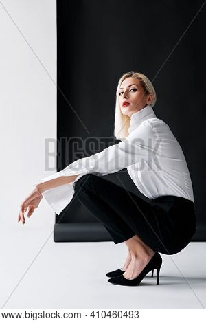 Sexy Blonde Woman With Red Lips Wearing White Shirt And Black Classic Pants Posing On Black And Whit