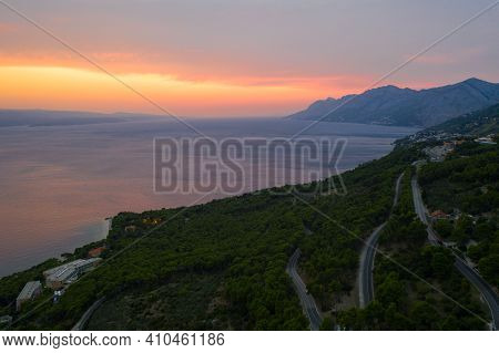 Beautiful Sunset View At The Seacoast. Splendid Orange Sky, Mountain Silhouettes, Endless Sea. Beaut