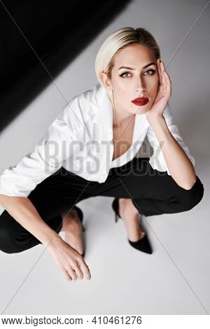 Top View Portrait Of Daring Trendy Woman Posing On White Studio Background Sitting On Floor. Gorgeou