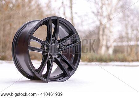 New Stylish Black Brushed Aluminum Alloy Wheel, On White Snow. Winter. Auto Tune Up Services
