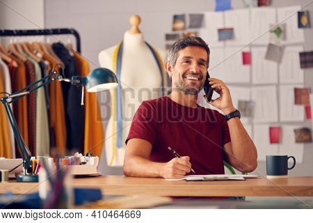 Mature Male Fashion Designer In Studio Working On Sketches Or Documents At Desk Making Phone Call