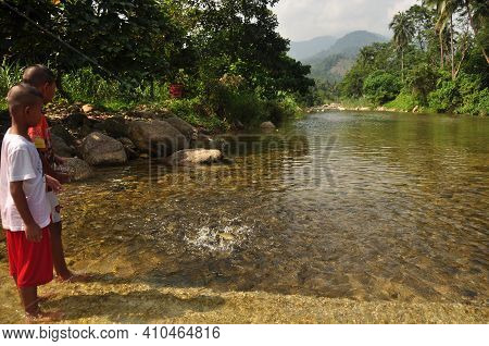 Nakhonsithammarat, Thailand - June 7, 2014: Kids In Shallow Clear Water Of Pond, View Of Little Ethn