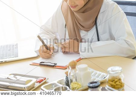 Young Asian Woman Muslim Doctor Smile While Working On Laptop And Taking Notes At Hospital, Medicine