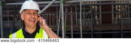 Panoramic web banner male builder, construction worker, contractor or architect on building site talking on his cell phone panoramic header