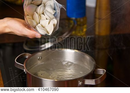 Pouring Dumplings From The Packaging Into Pots Of Boiling Water. Boiled Dumplings In A Pan