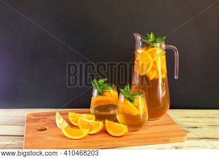 Summer Orange Lemonade In Pitcher And  Glasses And Fresh Oranges Near On Aged Wooden Table On Dark B
