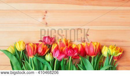 Colorful Spring Tulip Flowers As Border On Wooden Background. Top View, Copy Space.