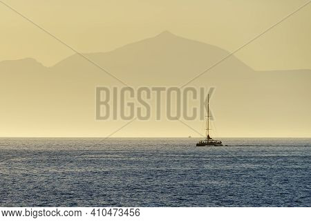 Catamaran Sailing In The Blue Sea With The Silhouette Of A Huge Island On The Horizon, Tenerife Isla