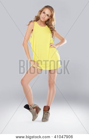 Beautiful leggy fashion model with long curly blonde hair posing in a skimpy yellow miniskirt and boots, studio full body portrait