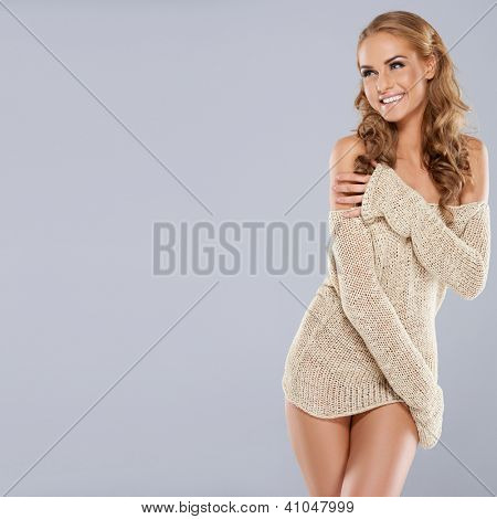 Playful beautiful blonde model laughing as she wraps her arms around the skimpy trendy off the shoulder top that she is wearing