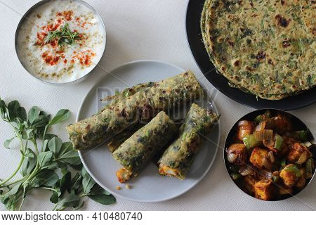 Whole Wheat Methi Thepla Rolls With Paneer Capsicum Filling And A Bowl Of Masala Curd.
